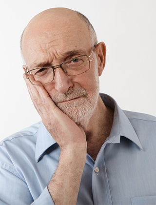 Older man in pain holding jaw
